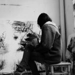 La artista Sandra Partera en frente de una de sus obras con postura reflexiva.